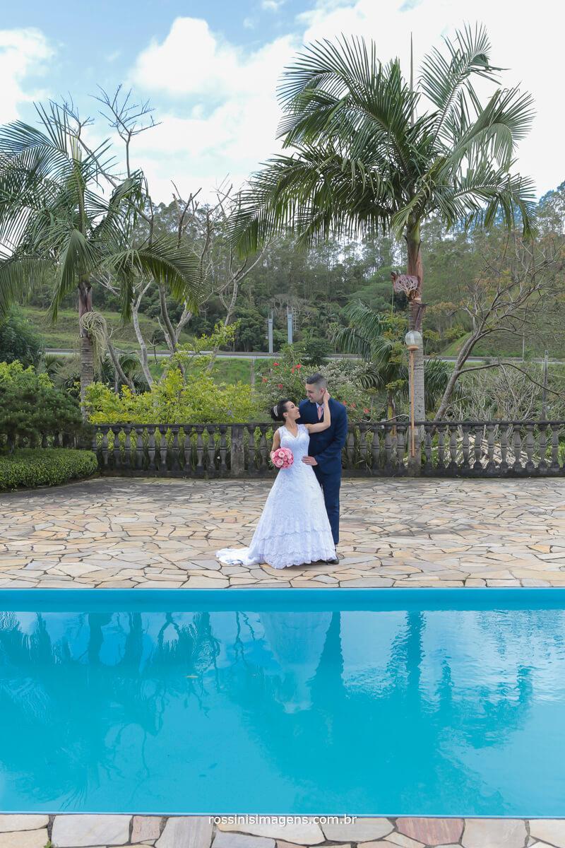 fotografia dos noivos juntos em frente a piscina e noiva com o buquê