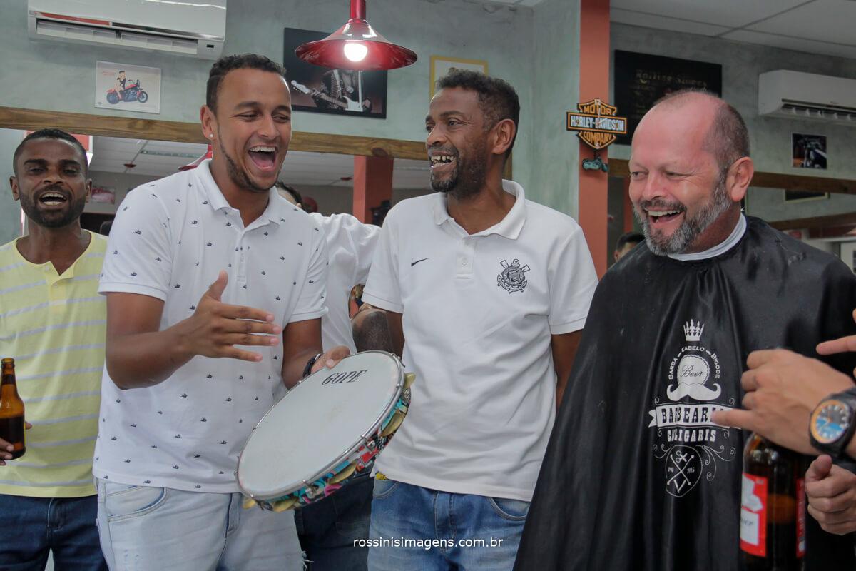 dia do casamento noivo no dia do noivo na barbearia com amigos, tocando o pagode