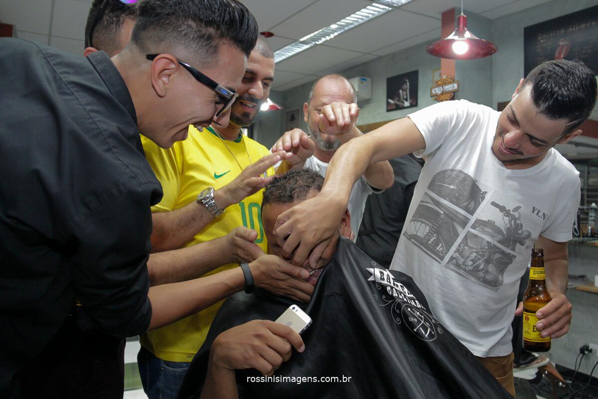 padrinhos fazendo brincadeiras com o noivo na barbearia no dia do casamento making of