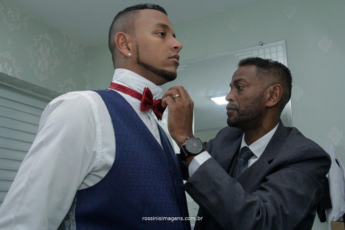 pai do noivo colocando a gravata borboleta em seu filho no dia do casamento