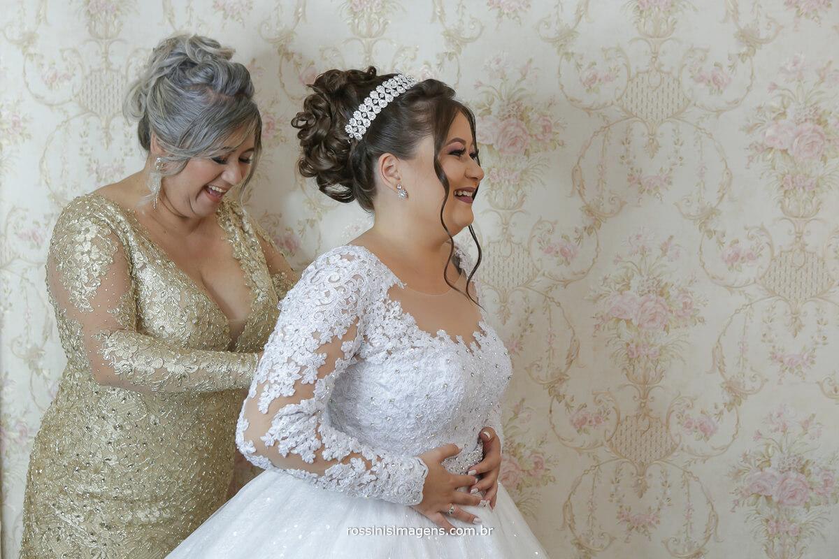 mae ajudando a fechar o vestido da noiva, mae fechando vestido da filha