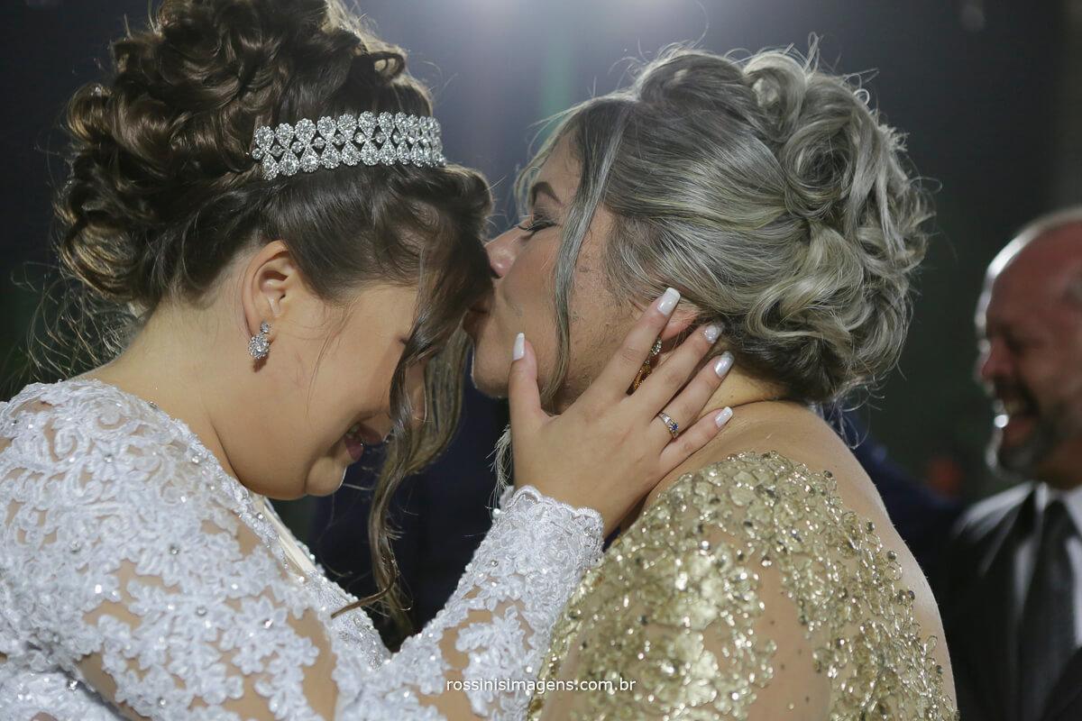 mae dando beijo na testa da sua filha a noiva