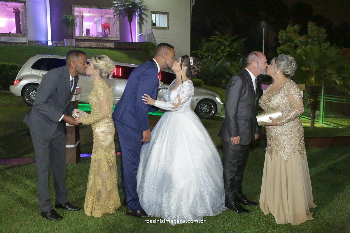 fotografia coletiva com os pais e os noivos dando um selinho