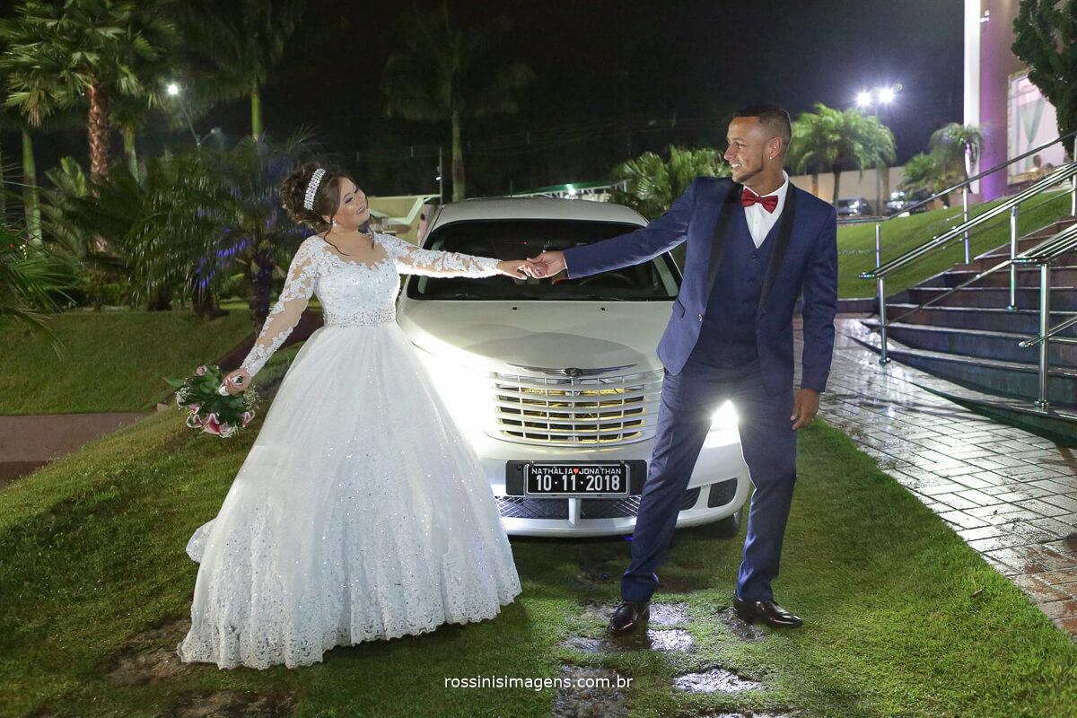 noivos na frente da limousine brincando de dança com o buquê