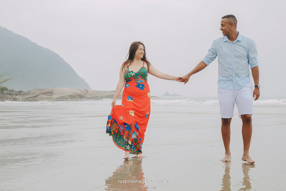 noiva de vestido vermelho florido em ensaio na praia