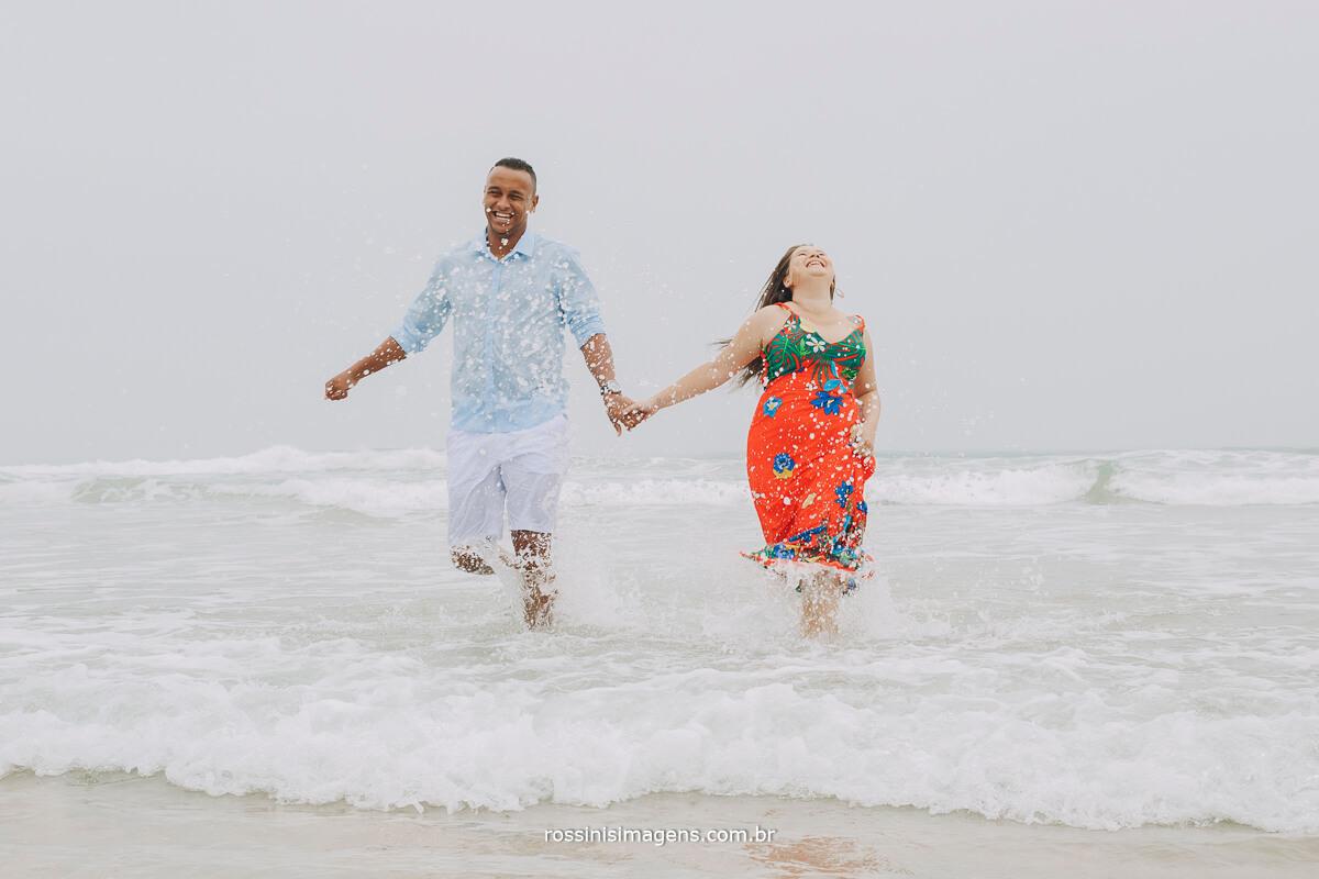 casal de noivos saindo correndo do mar na praia de Iporanga em são paulo