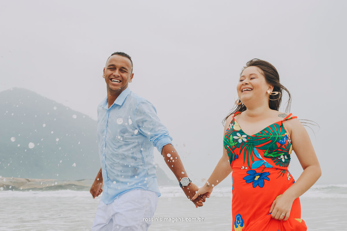 noivos correndo olhando um ao outro saindo do mar na praia em dia nublado um ensaio incrível realizado na praia