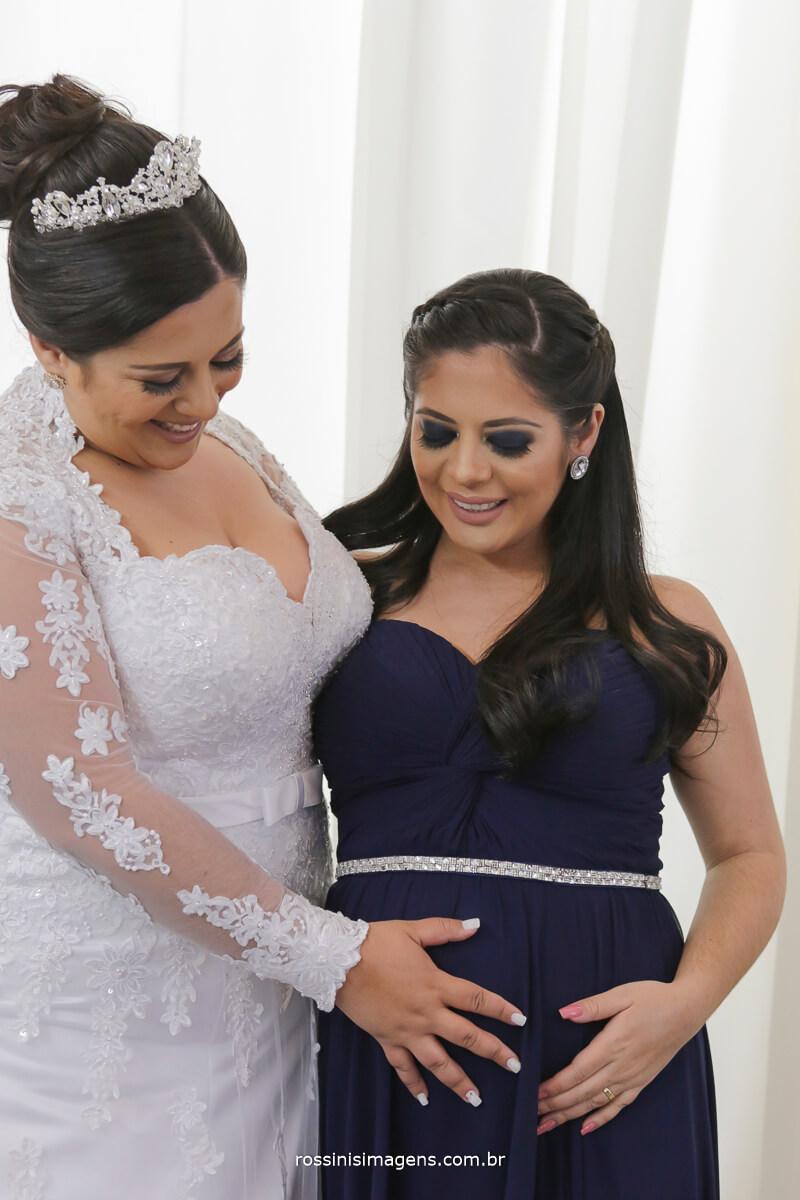noiva com a mão na barriga da irmã que esta gravida, madrinha gravida, irmã gravida, gravidez, gestação