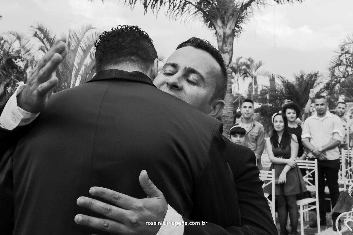 abraço do irmão da noiva no noivo que esta no altar