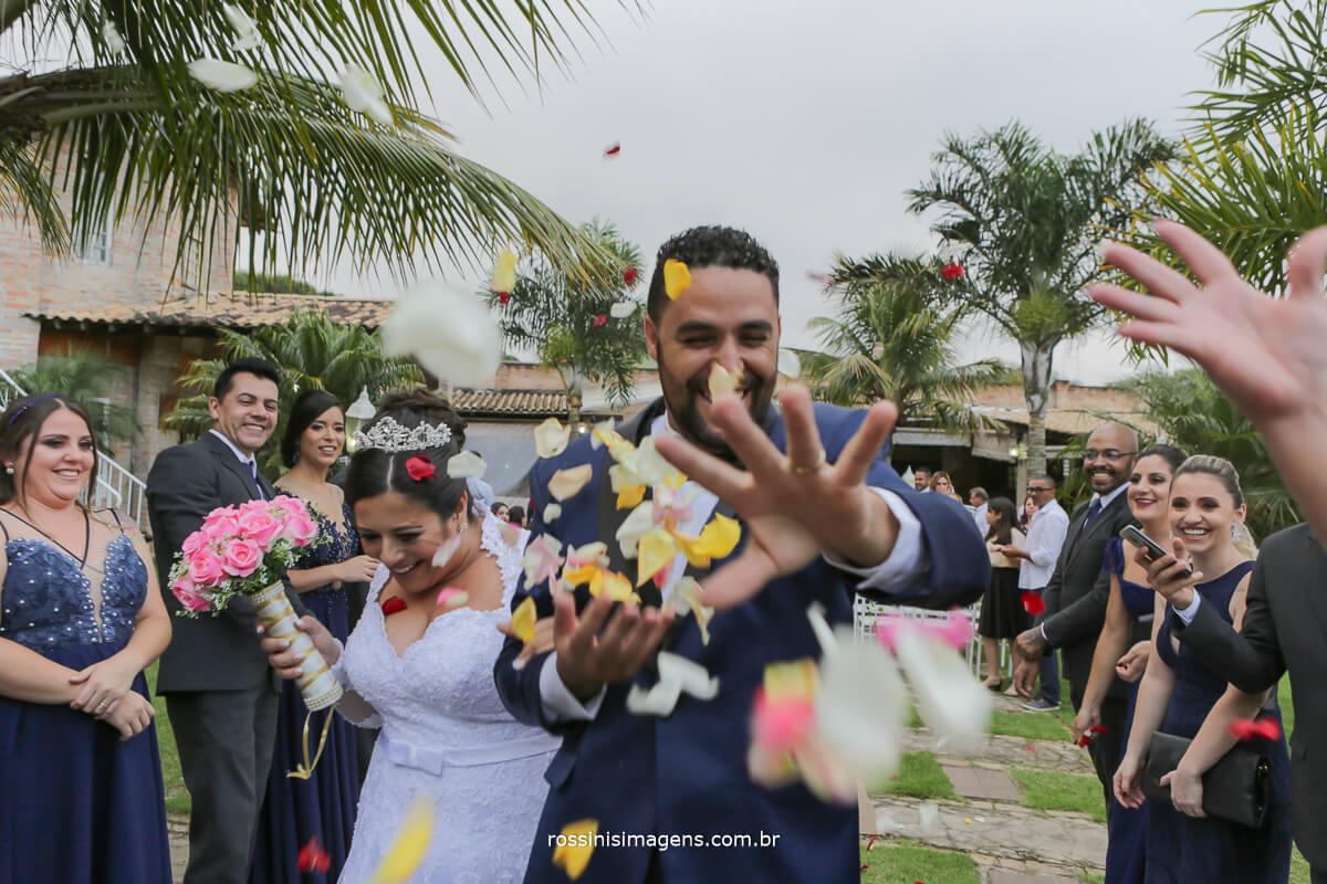 saida dos noivos com petalas de flores coloridas, padrinhos animados
