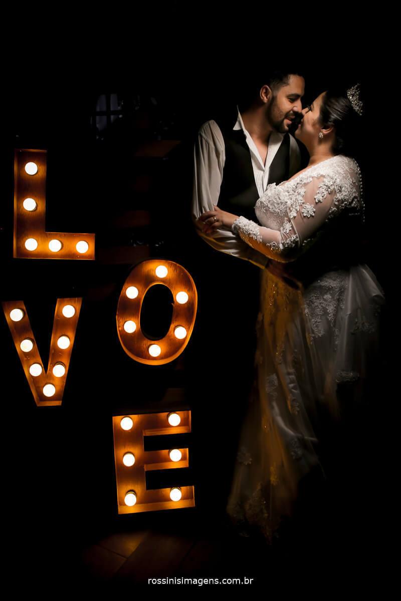 fotografia do casal camila e Ramon ao lado do letreiro love com luz, love iluminado, foto de casal no love, foto de noivos love acesso