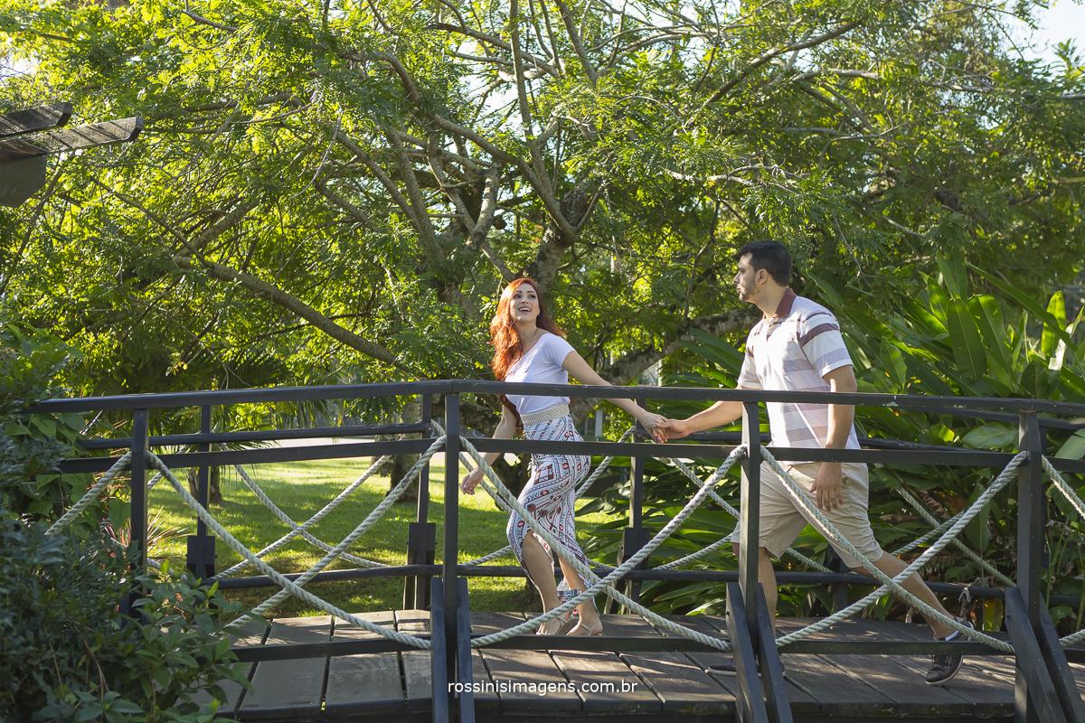 ensaio casal lili e diogo na praia, casal correndo em ponte