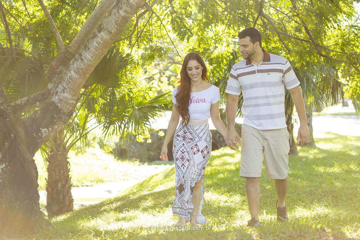 casal caminhando no gramado em dia de sol