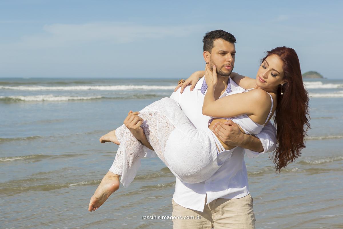 fotografo de ensaio casal pre casamento e praia noivo com a noiva no colo na beira do mar