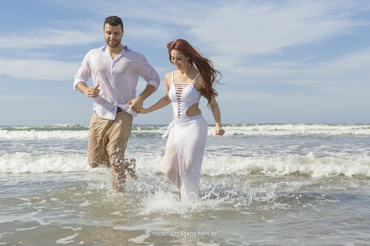 fotografo de ensaio casal pre casamento e praia, casal correndo no mar