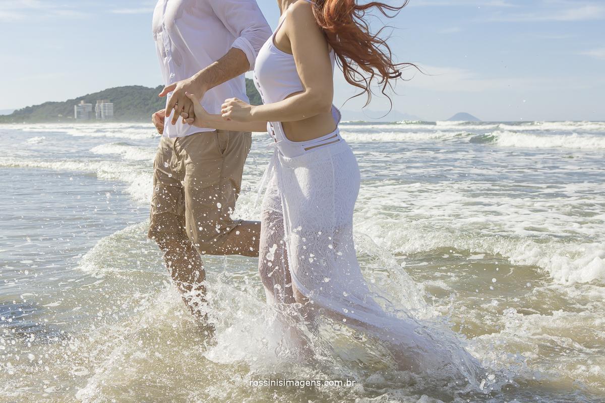 casal correndo de lado no mar, fotografia na praia, dia de sol, praia linda agua clara ceu azul