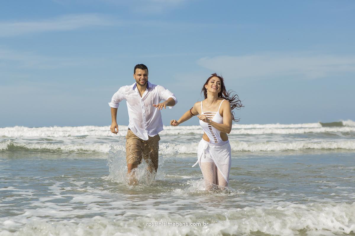 aquele ensaio pre casamento top fotografia incrivel do casal correndo saindo do mar, com um ceu azul espetacular rossinis imagens