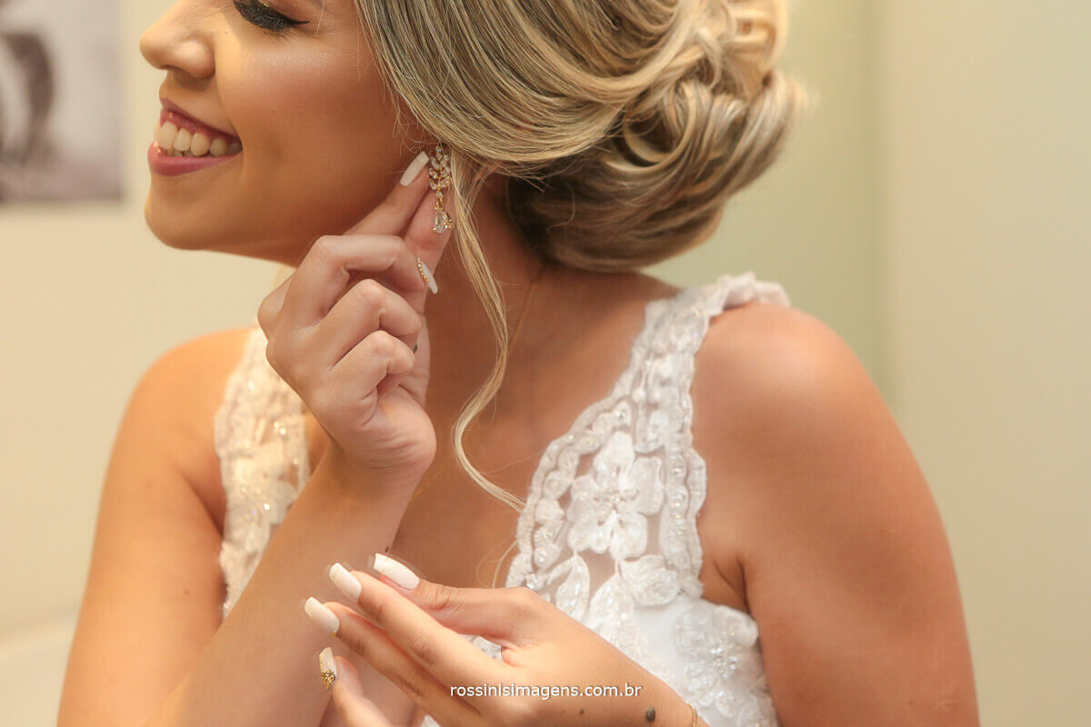 noiva de vestido branco colocando o brinco sorrindo, feliz noiva rossinis imagens