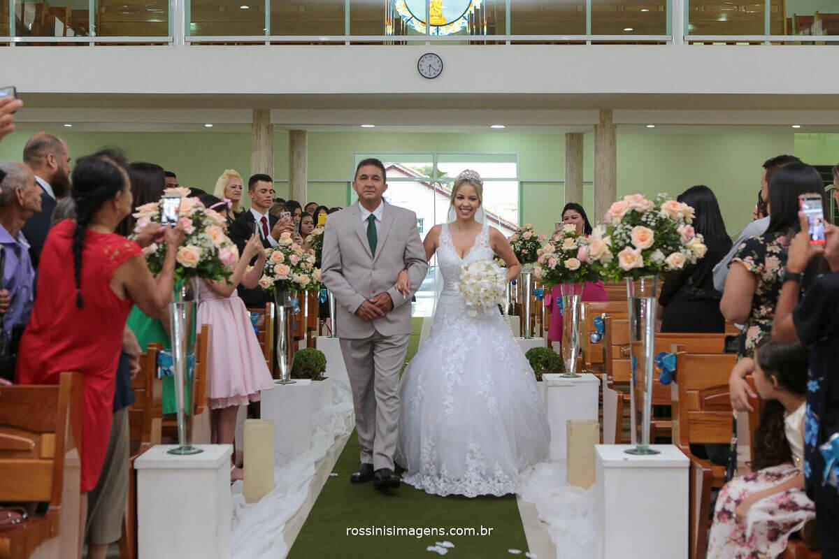 entrada da noiva junto com seu pai sorridente e feliz