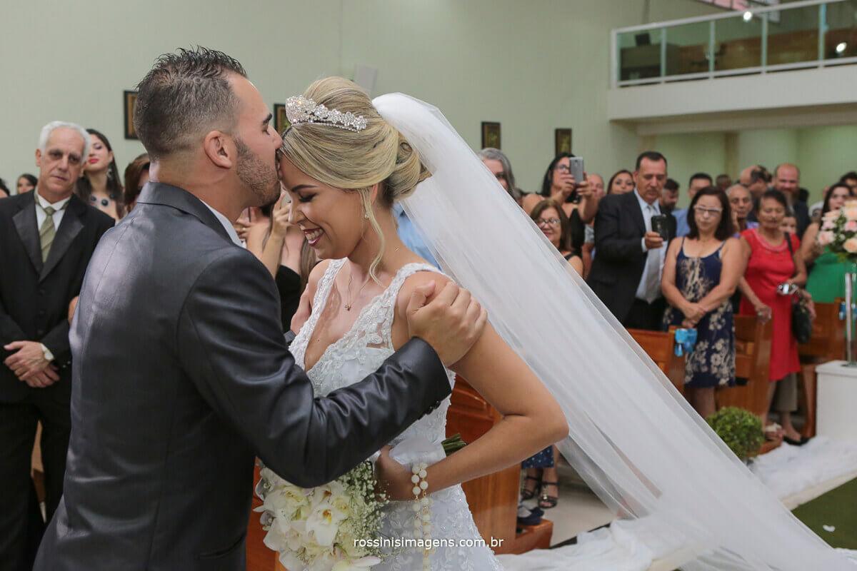 noivo recepcionando a noiva com um charmoso beijo na testa no altar