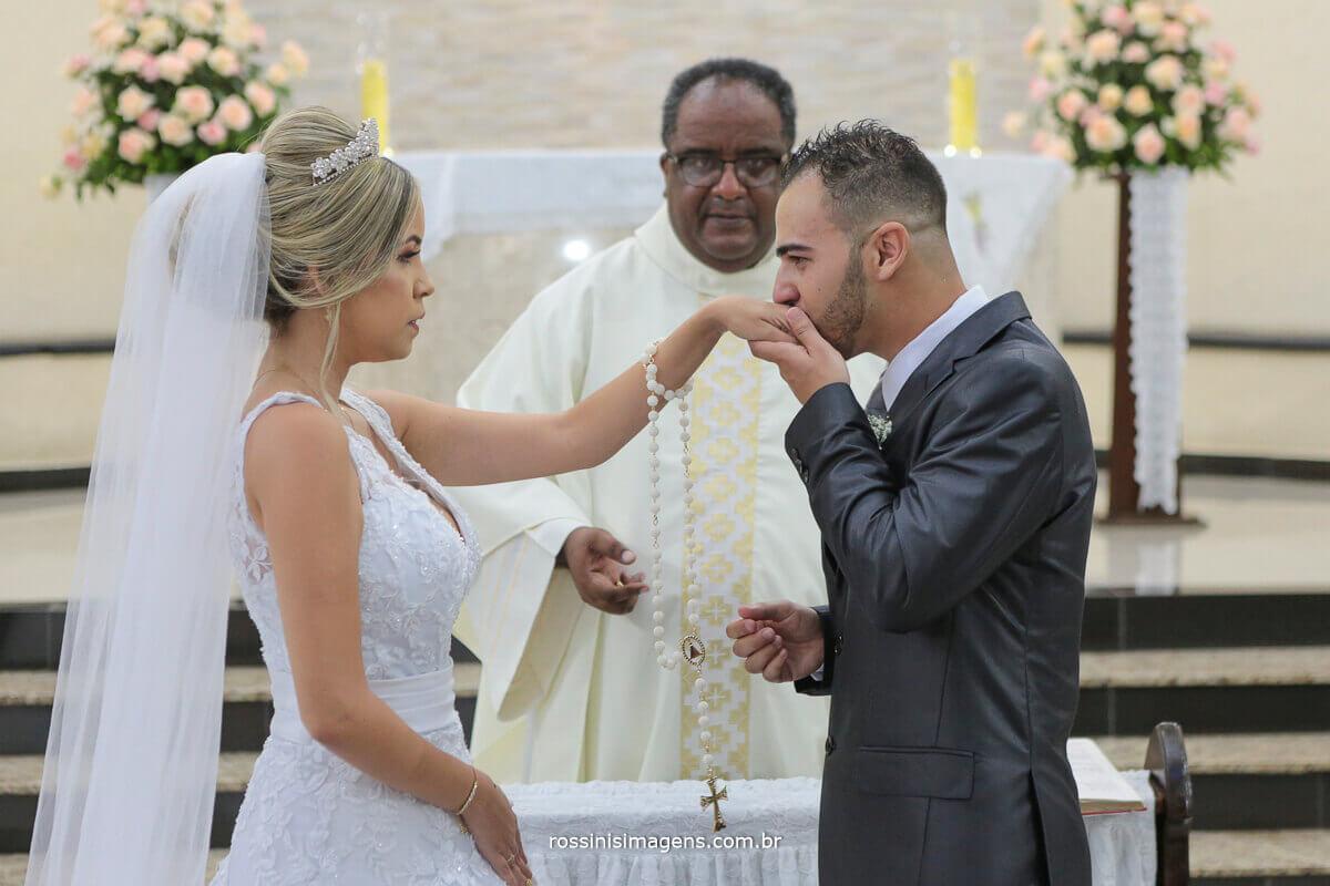fotografia do noivo beijando a aliança que colocou na mão da noiva