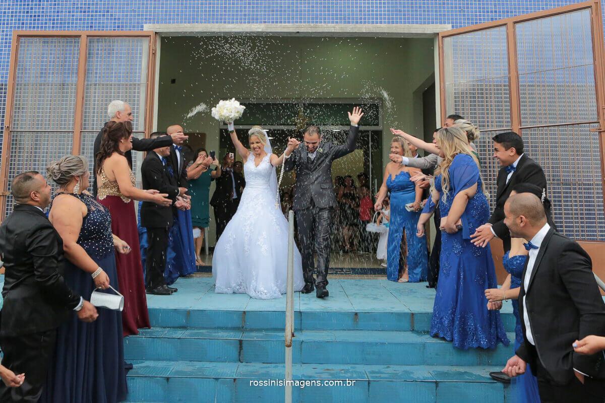 saída dos noivos super animadas com chuva de arroz,