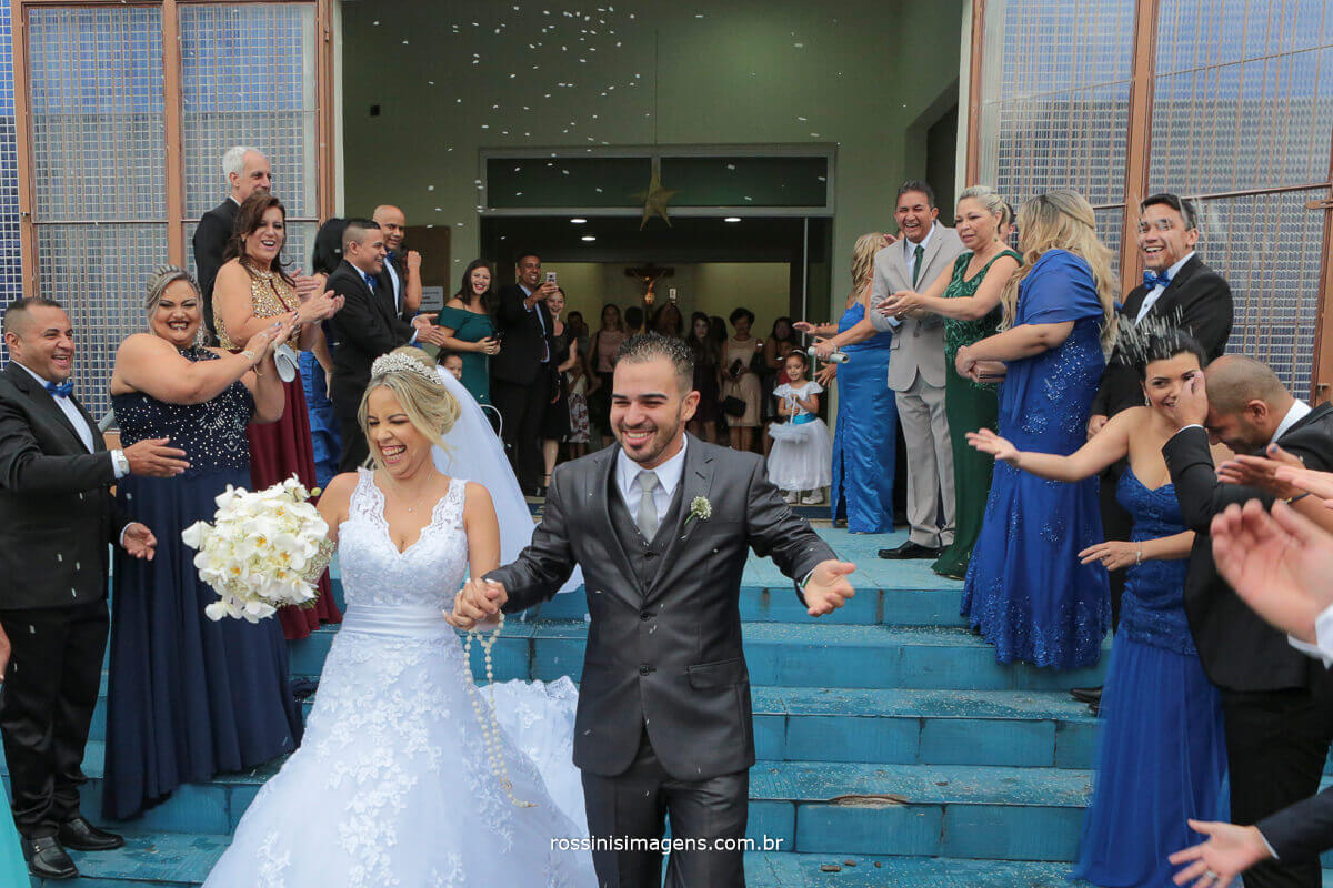 padrinhos jogando arroz nos noivos, na saída
