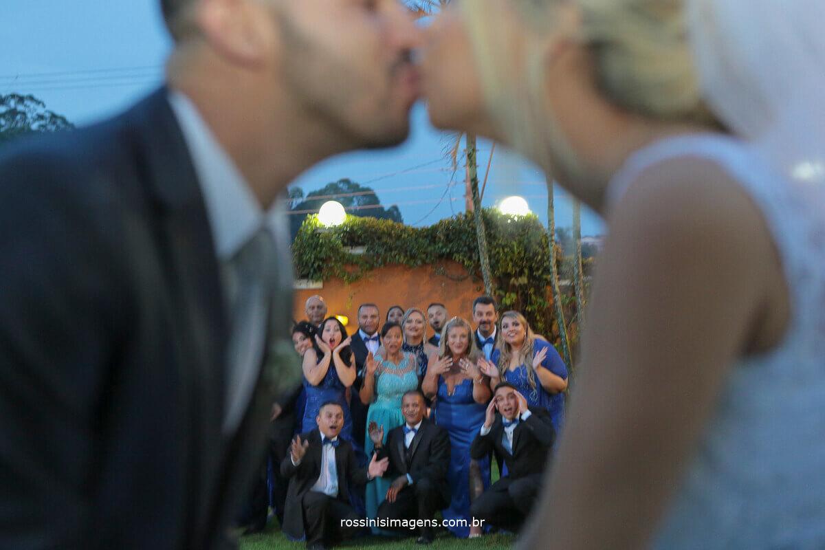 fotografia de casamento, noivos dando beijo e os padrinhos ao fundo com cara de surpresos