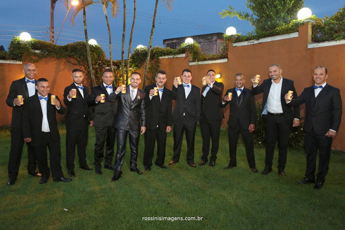 fotografia coletiva com os padrinhos e o noivo todos com latinha de cerveja skol na mão