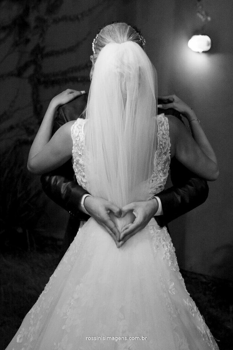 noivo fazendo um coração atras do vestido da noiva jennifer e felipe em poá casarão baronesa