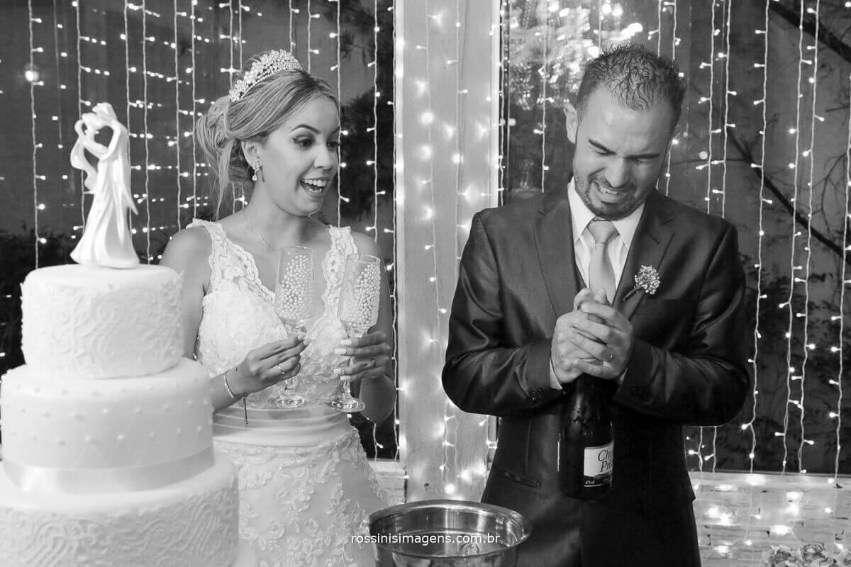 noivo fazendo careta para abrir a champanhe, e noiva rindo