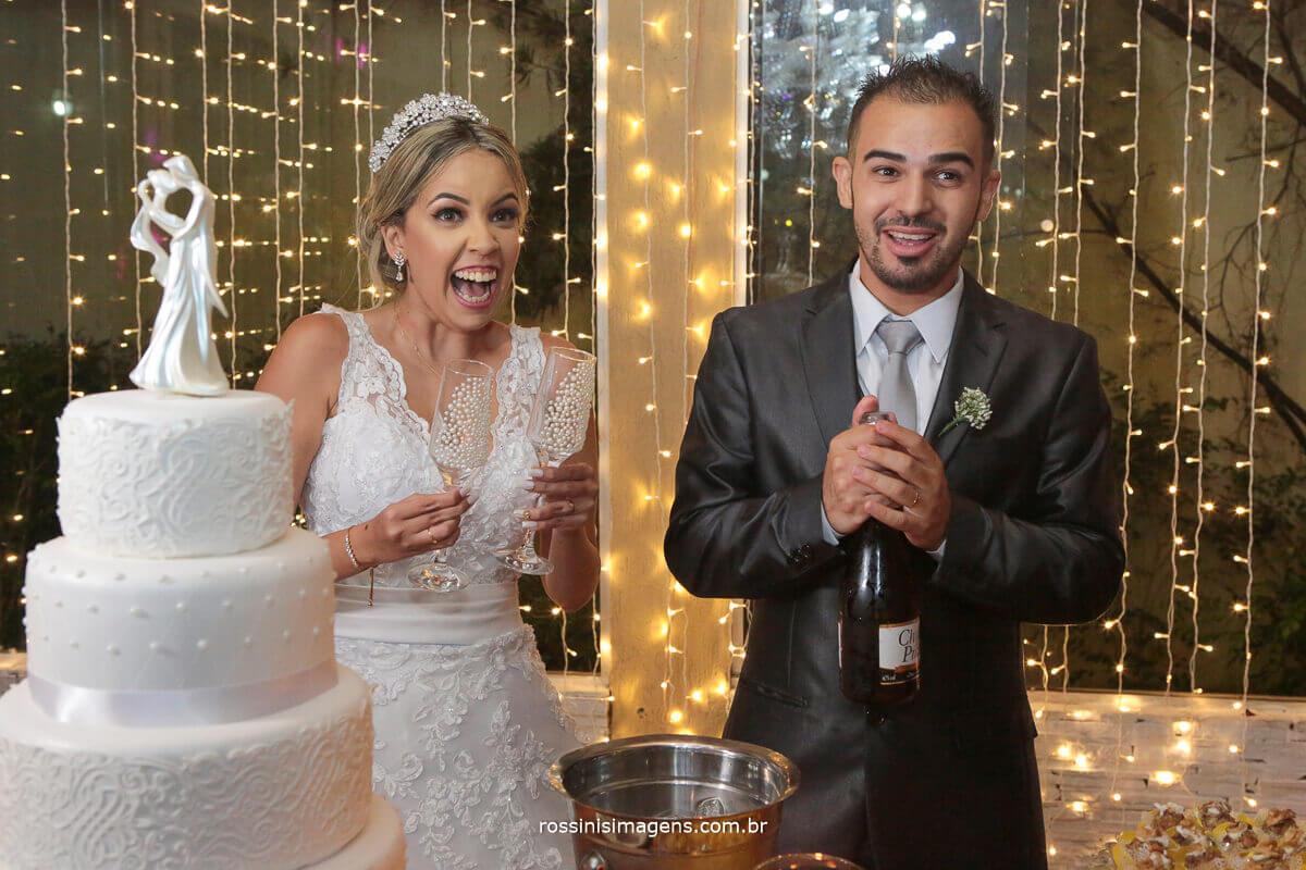noivo feliz abrindo champanhe e noiva surpresa e feliz foto no bolo com taça personalizada