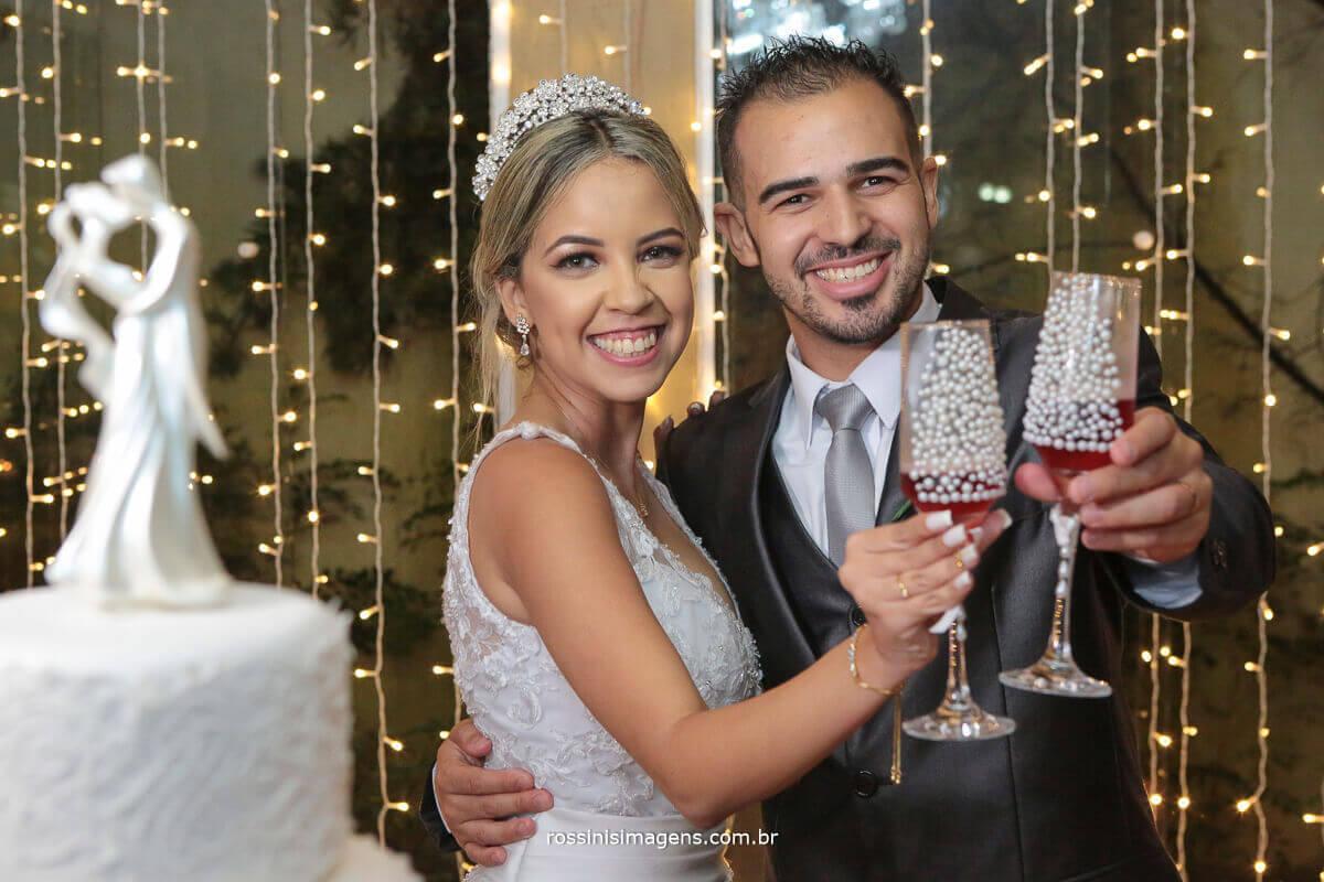 noivos brindando com taça personalizada na mesa do bolo, viva os noivos, rossinis imagens foto de casamento em suzano, poá, mogi, ferraz
