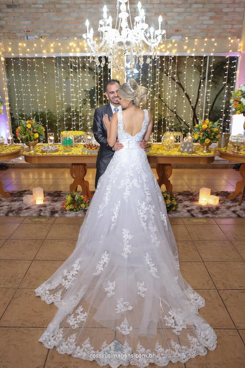 noiva mostrando parte de traz do vestido branco com rendas mesa do bolo, noiva e noivo