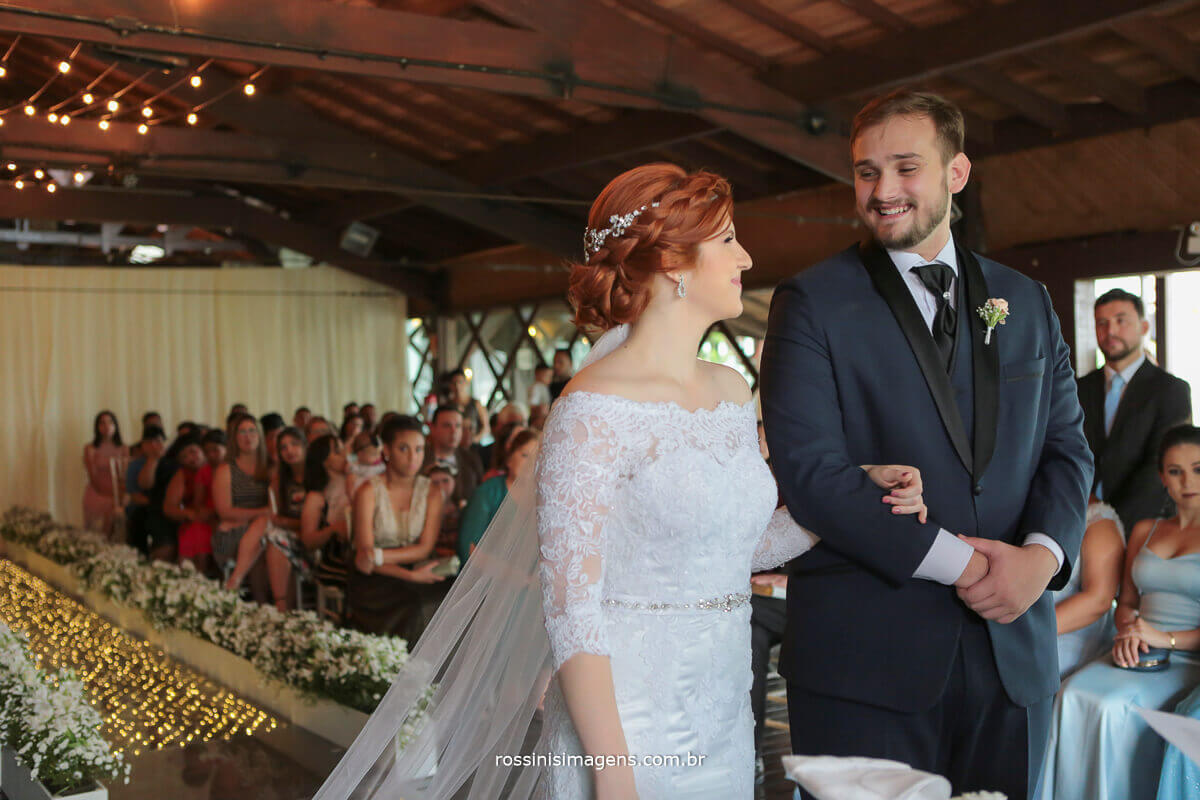 noivos na cerimonia de casamento se olhando e sorrindo