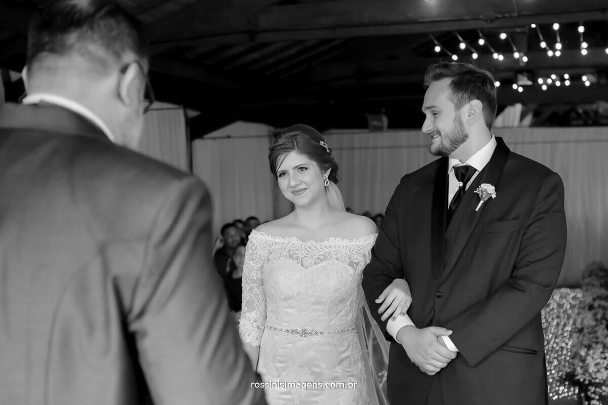 pai celebrando o casamento do filho e noivo olhando a noiva