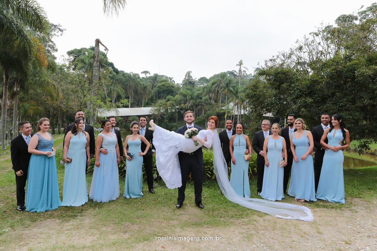 padrinhos e madrinhas e o noivo com a noiva no colo