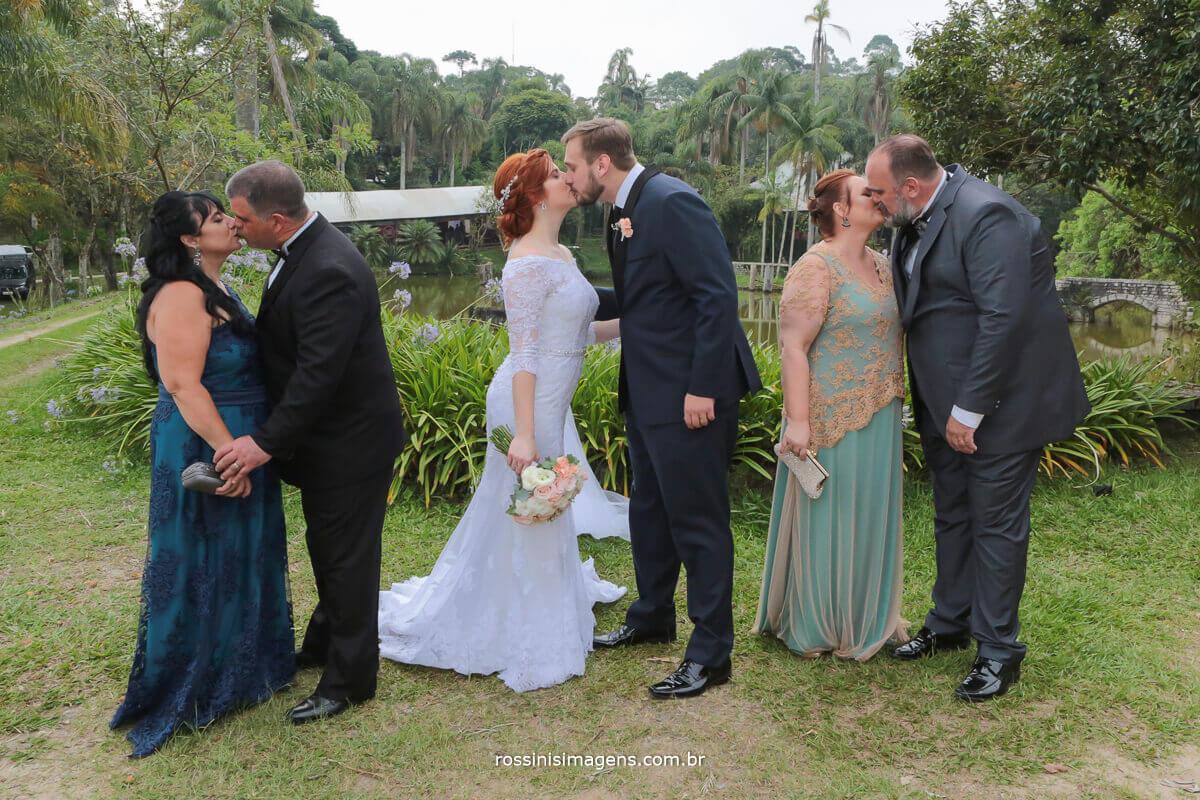 pais dos noivos dando beijo e noivo dando selinho