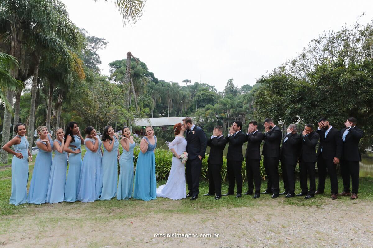 padrinhos e madrinhas puxando os noivos evitando o beijo