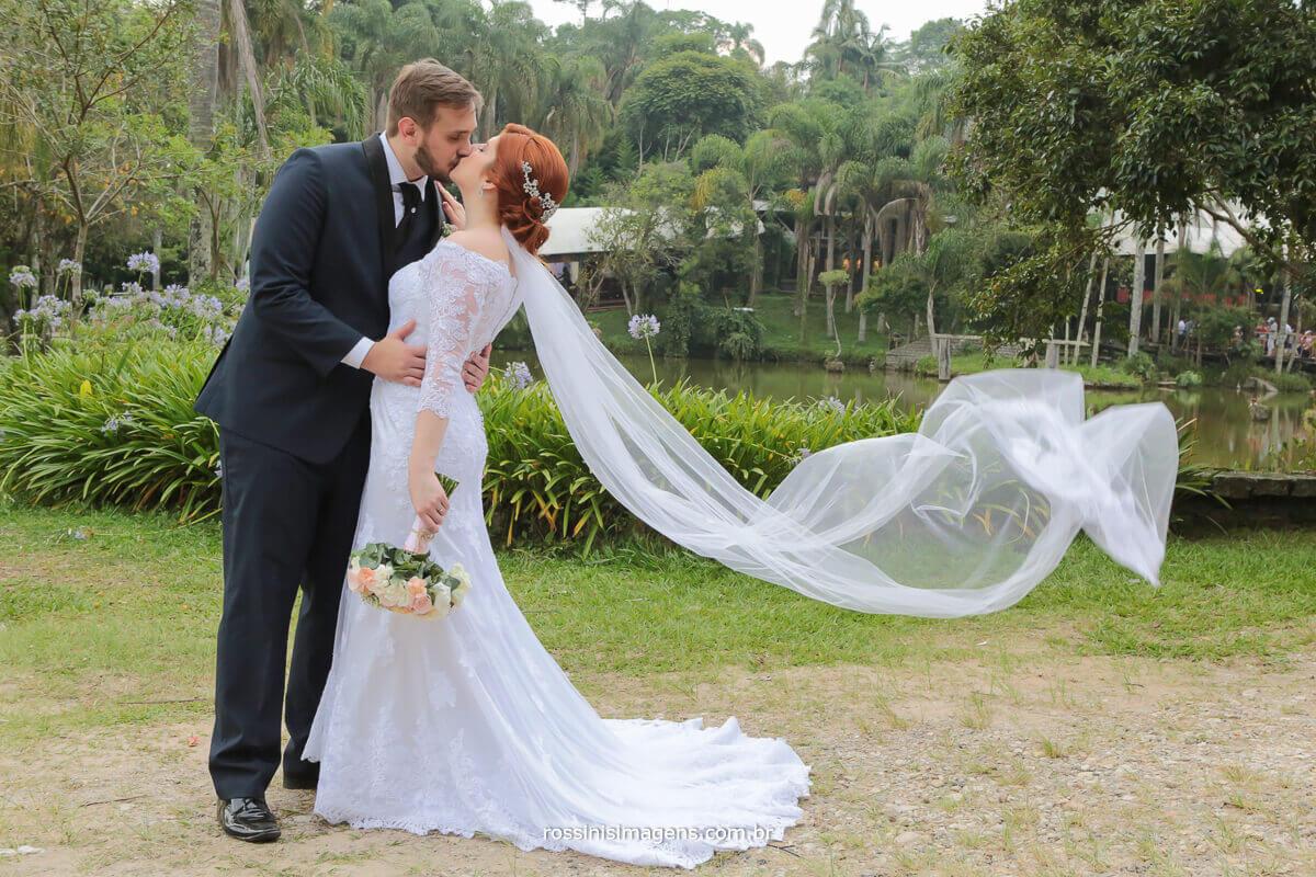 casal renata e kevin dando beijo eo véu voando na sessão de fotos
