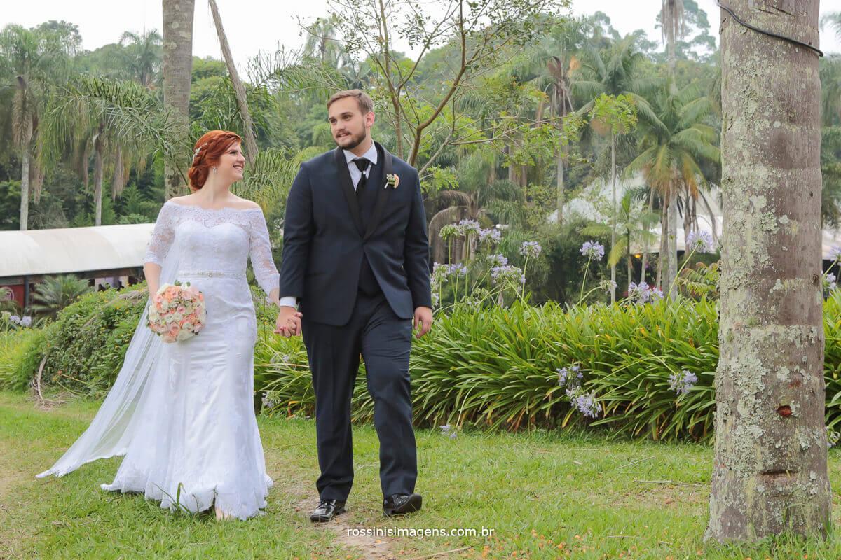 casal caminha juntos na sessão de fotos apos a cerimonia em direção a recepção e festa