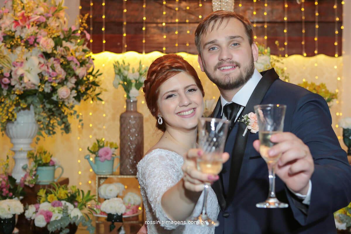 brinde dos noivos na mesa do bolo com decoração da fv decorações