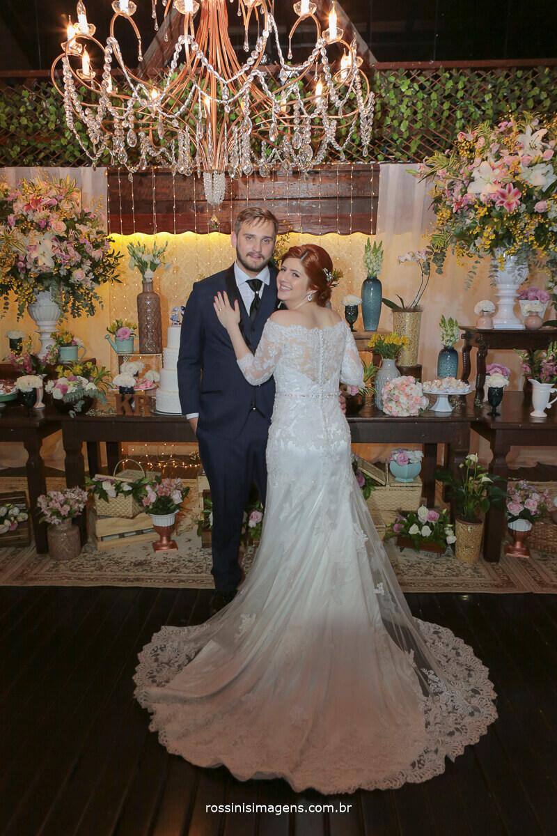 sessão de fotos dos noivos na mesa do bolo noiva mostrando os detalhes nas costas do vestido, rossinis