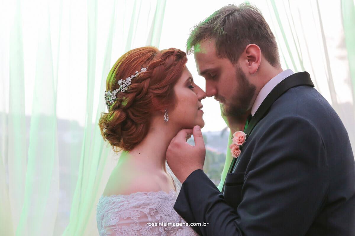 fotografia colorida de casal apaixonado e romantico, noivo fazendo carinho no rosto da noiva