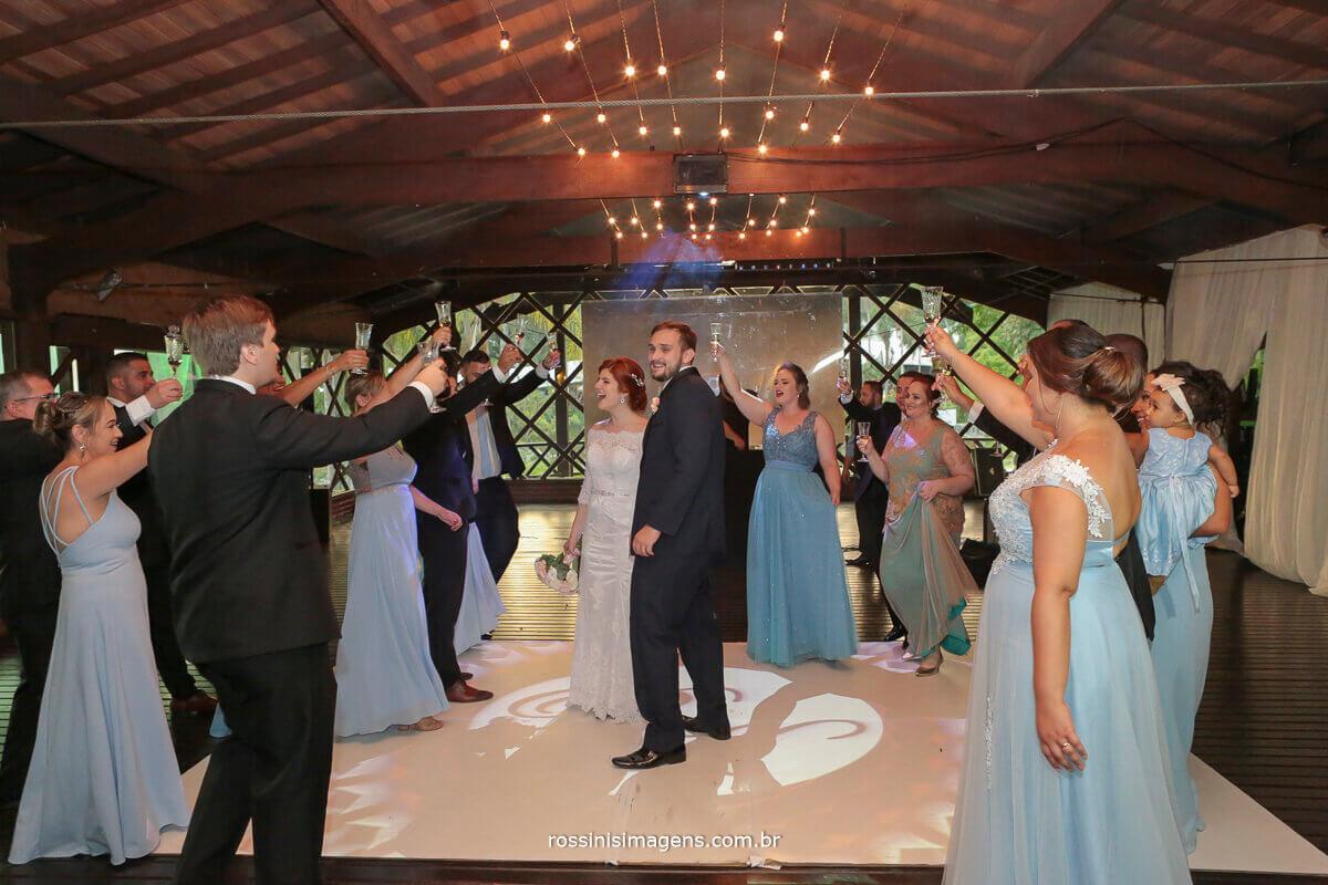 padrinhos na pista de danca fazendo um brinde junto aos noivos