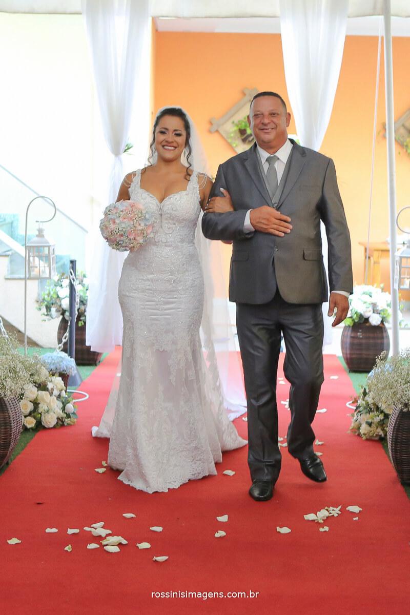 entrada da noiva com o pai no tapete vermelho e emocionada