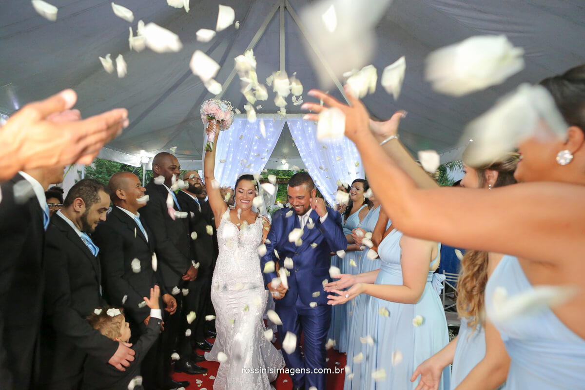 saida dos noivos com petalas, brancas, momento unico e super animado, padrinhos e madrinhas seguindo o padrão