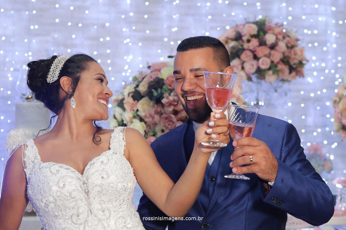 brinde do casal na mesa do bolo com tacha de champanhe