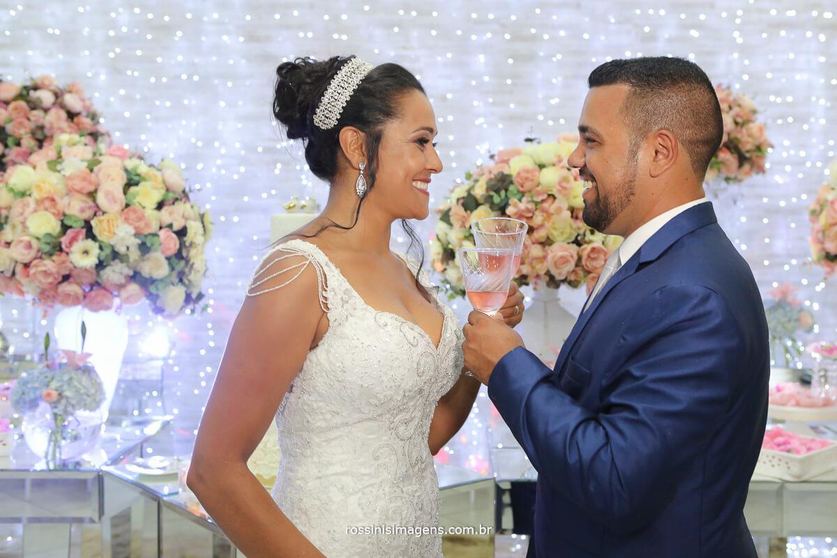 noivos cruzando as taças no brinde de casamento