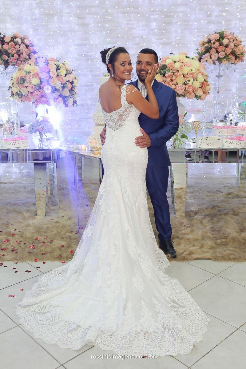 noivos em frente a mesa do bolo, noiva mostrando os detalhes do vestido, parte de traz do vestido